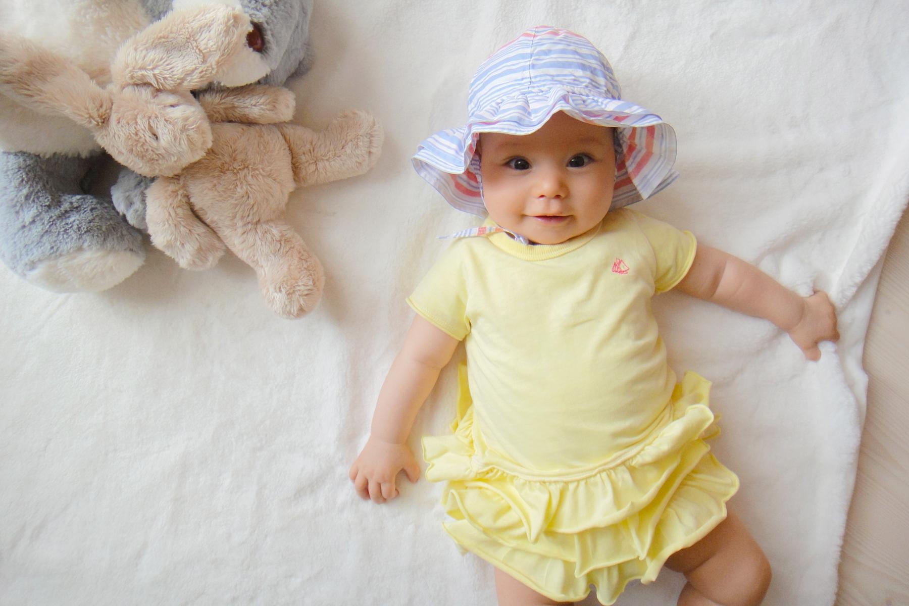 Bébé habillé en robe Petit Bateau, chapeau Sergent Major et doudou lapin Moulin Roty