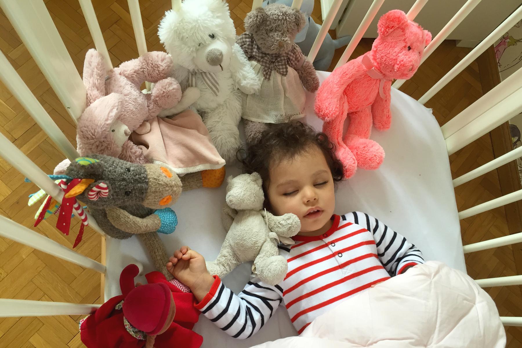Bébé habillé en Petit Bateau et ses doudous