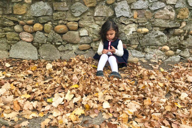 Enfant sur les feuilles au parc de Beauregard en automne