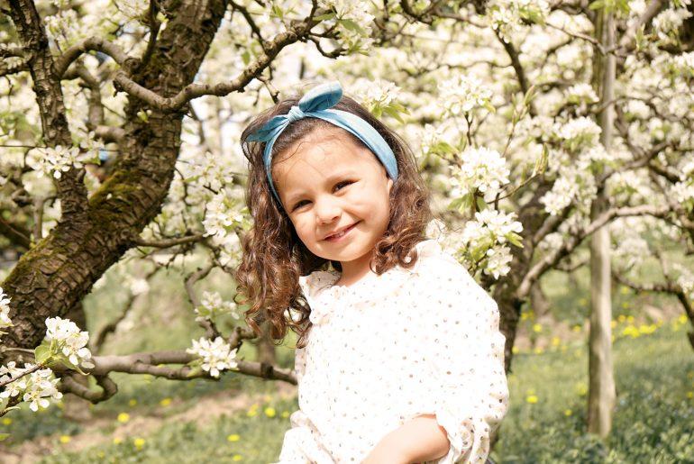 Vacances de Pâques - Petite fille au milieu des arbres fruitiers