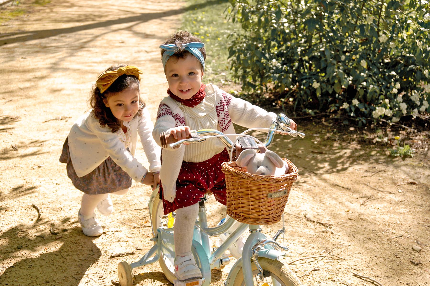 Petite fille à vélo poussée par sa soeur