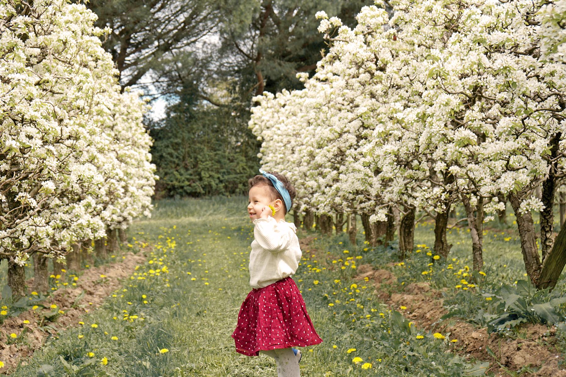 Petite fille au milieu des arbres fruitiers