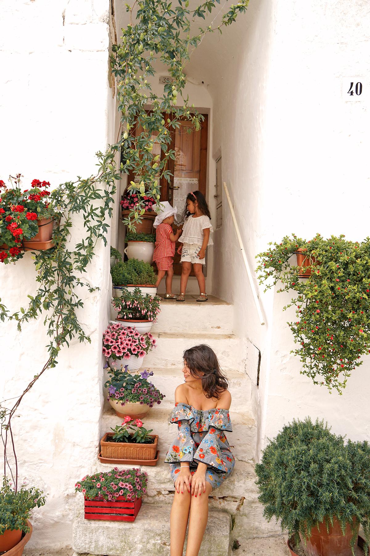 Mère et Petites filles et les pots de fleurs à Alberobello, Pouilles Italie