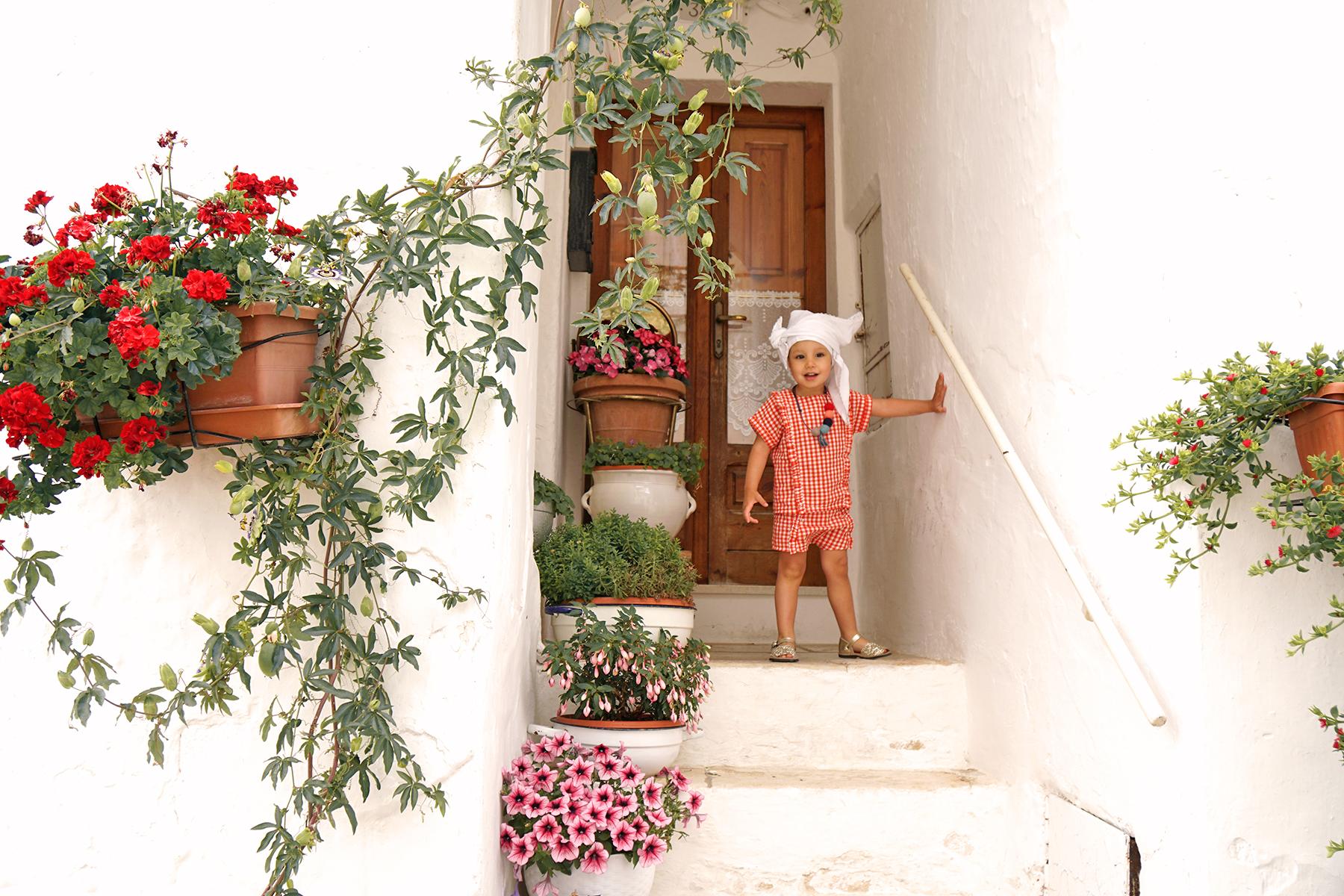 Petite fille et les pots de fleurs à Alberobello, Pouilles Italie