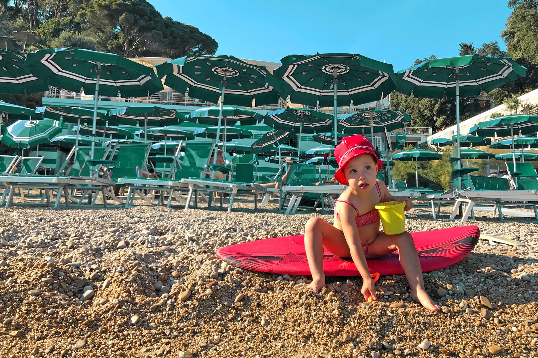 Petite fille sur un surf à la plage