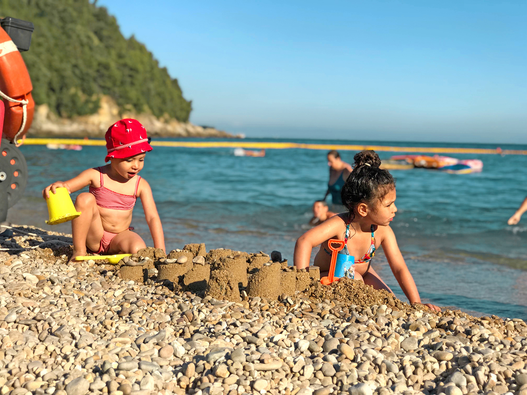 2 soeurs font un château de sable