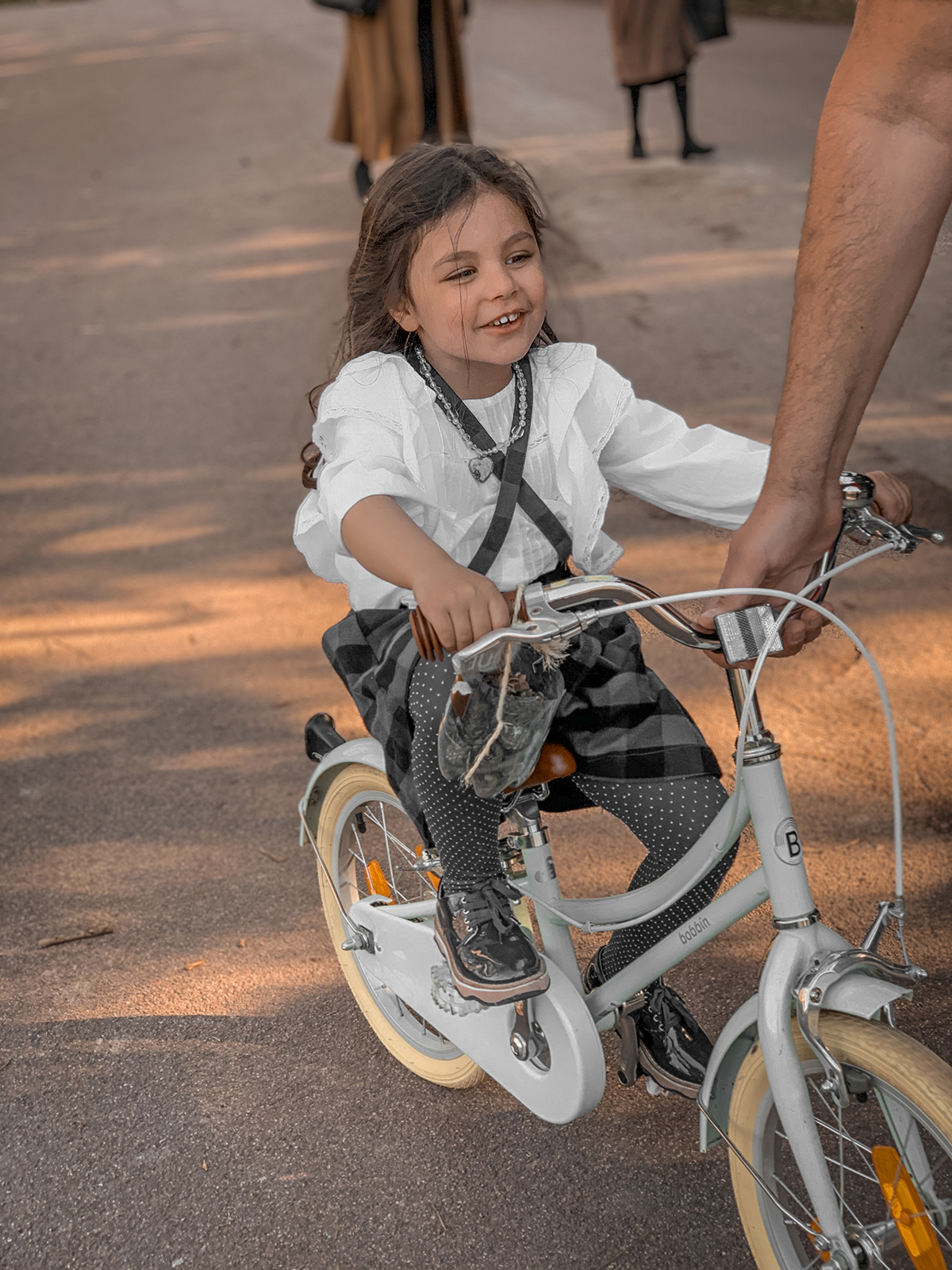 Romy sur son vélo. Papa aide au démarrage