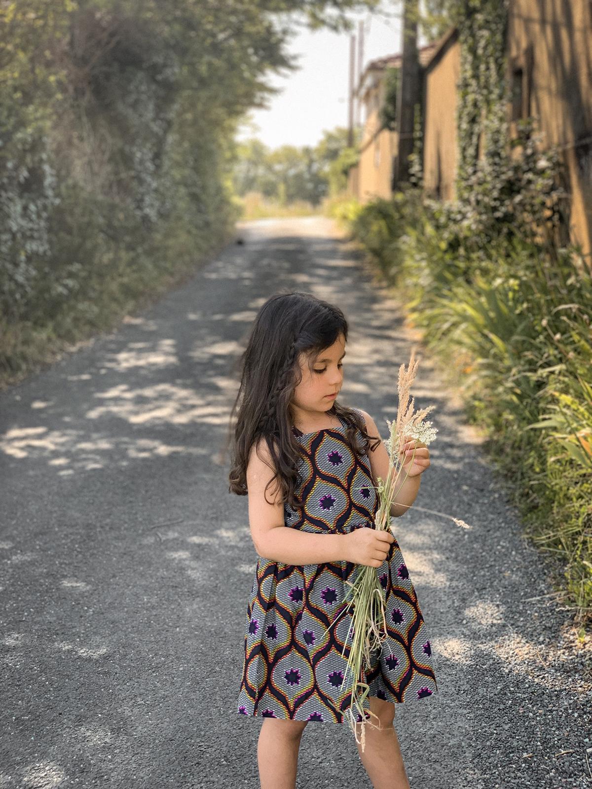 Romy habillée en wax, à la campagne après l'école